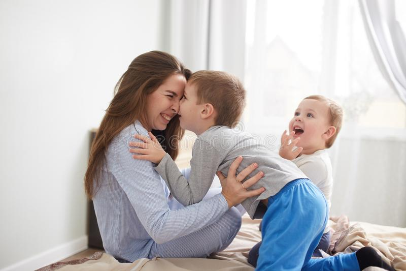 Den unga h?rliga modern och hennes tv? ikl?dda pyjamas f?r sm? s?ner har gyckel p? s?ngen i det ljusa hemtrevliga sovrummet royaltyfri foto