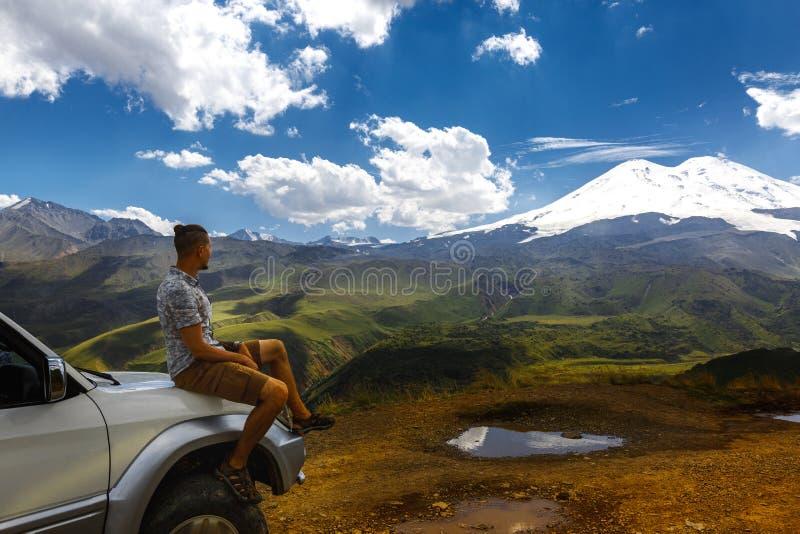 Den unga handelsresandemannen sitter på bilen och tycker om sikt av berg i sommar Elbrus region, norr Kaukasus, Ryssland royaltyfria bilder