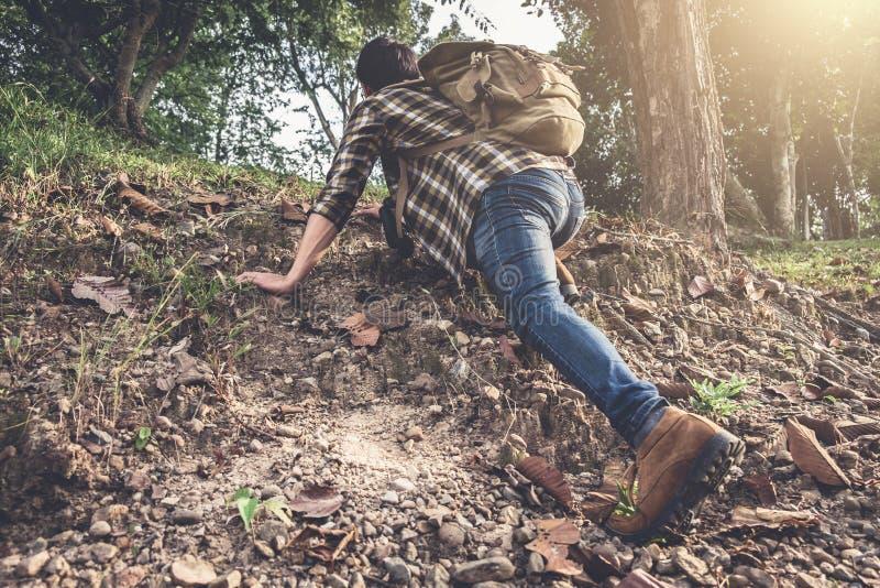Den unga handelsresanden med ryggsäcken klättrar med berget i för arkivbild