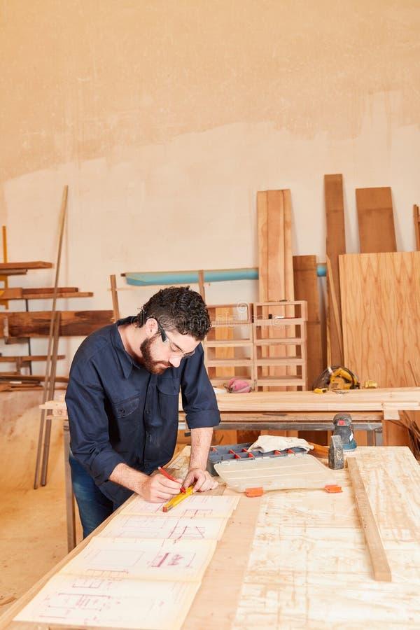 Den unga hantverkaren drar en ritning arkivfoto