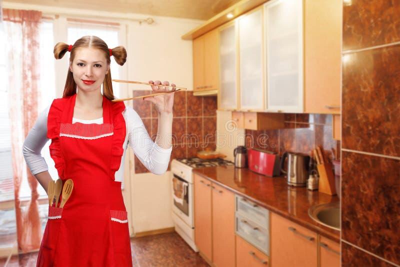 Den unga hemmafrun i ljust rött förkläde med roliga hästsvansar står arkivfoto