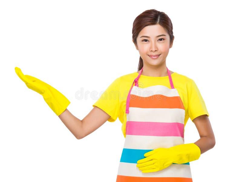 Den unga hemmafrun med den öppna handen gömma i handflatan med rubber handskar fotografering för bildbyråer