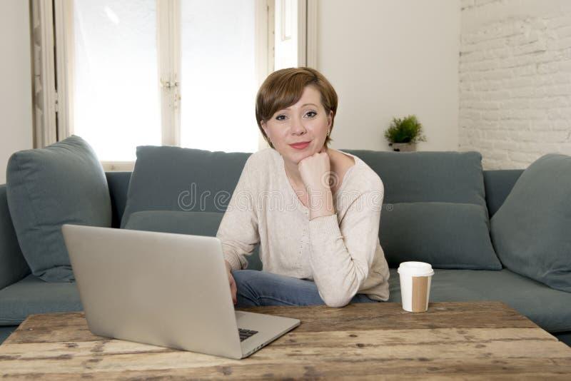 Den unga hemmastadda soffasoffan för den attraktiva och lyckliga kvinnan som gör något le för arbete för bärbar datordator, koppl royaltyfri fotografi