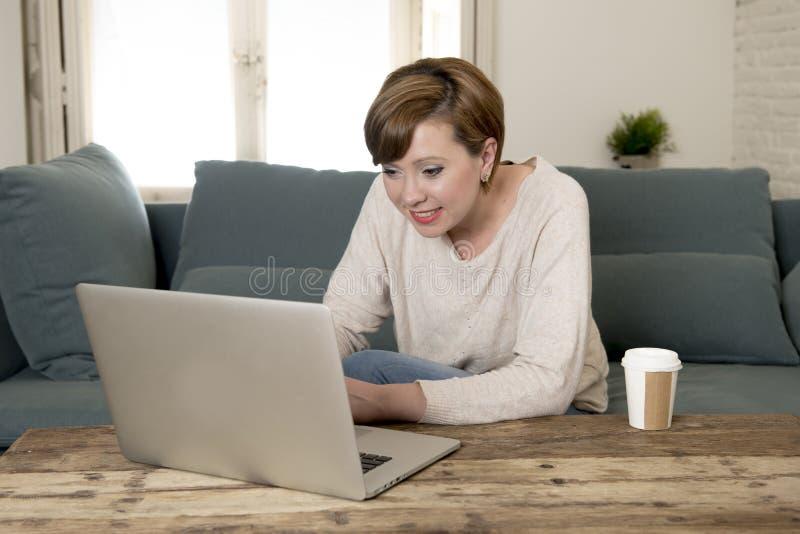 Den unga hemmastadda soffasoffan för den attraktiva och lyckliga kvinnan som gör något le för arbete för bärbar datordator, koppl royaltyfria foton