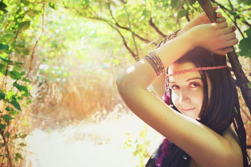 Den unga hippieflickan med fjädrar i hennes posera för hår som och för huvudbindel är utomhus- i soligt, parkerar och att se kame arkivbild