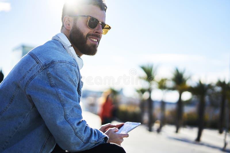 Den unga hipsterbloggerhandelsresanden i ett grov bomullstvillomslag och navigatör på smartphonen förband till internet 4G arkivfoton
