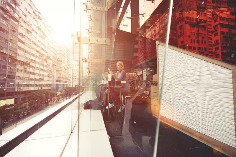 Den unga hipsterflickan använder mobiltelefonen under rekreation i kafé arkivbilder