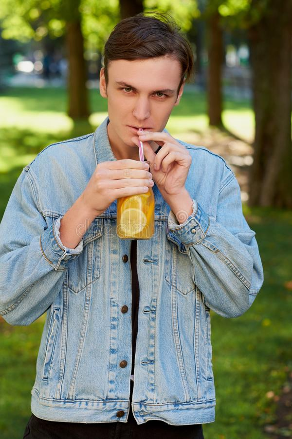 Den unga hipstermannen dricker sunt detoxte royaltyfria foton