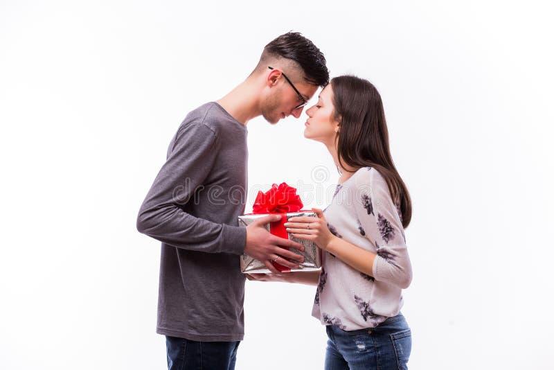 Den unga hipstermannen som ger en gåva semestrar på, hans flickvän Hon önskar kysser honom royaltyfri bild