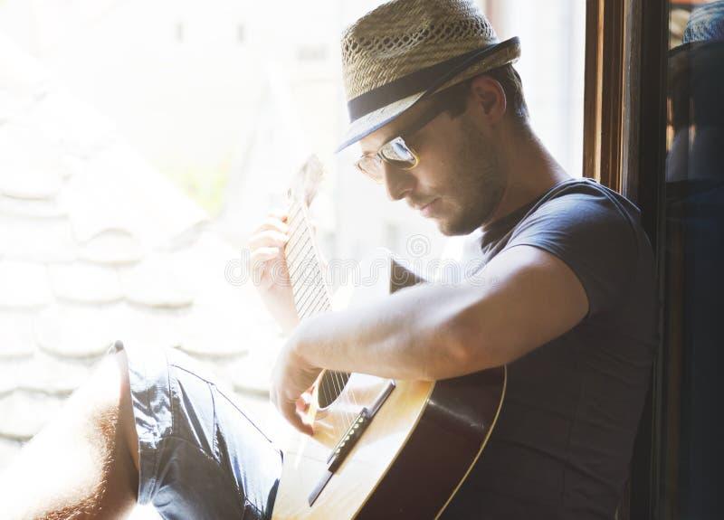 Den unga hipstermannen spelar gitarren royaltyfri foto