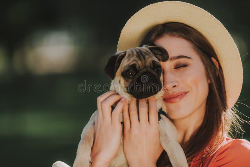 Den unga hundkapplöpningägaren kramar försiktigt hennes husdjur arkivbild