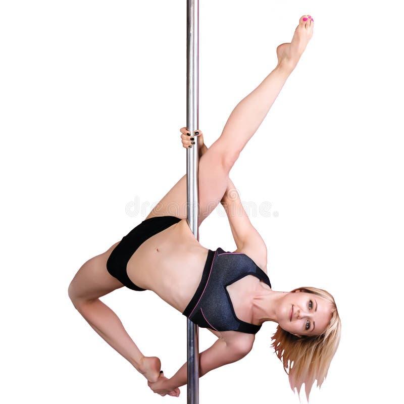 Den unga idrotts- blonda flickan som gör styrka, övar på en pylon arkivbild