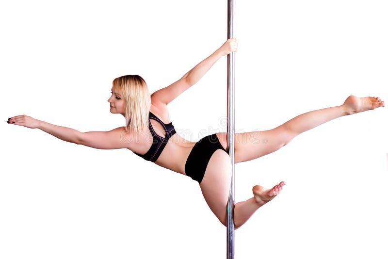 Den unga idrotts- blonda flickan som gör styrka, övar på en pylon royaltyfri foto