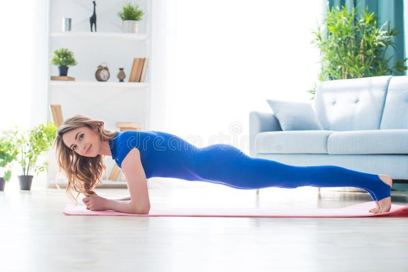 Den unga idrotts- flickakonditioninstruktören i blåa sportoveraller visar gymnastiska övningar för morgon i inre av rummet arkivfoto