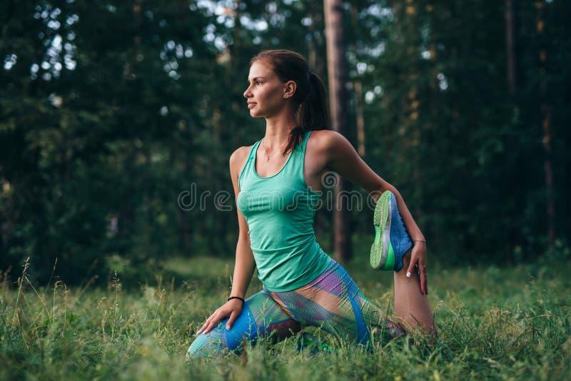 Den unga idrottskvinnan som värmer upp, för genomköraren som gör sträckning, övar sammanträde på gräs in, parkerar arkivbilder