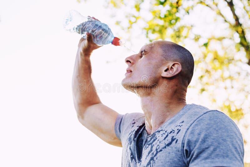 Den unga idrottsman nen är uppfriskande själv med vatten, sporten och sund livsstil royaltyfria foton