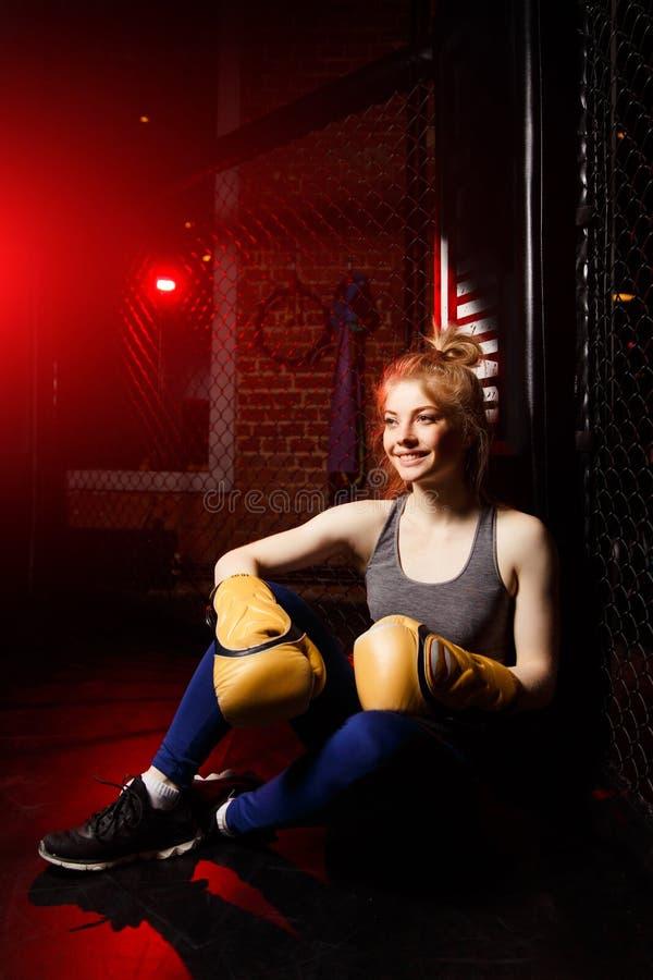 Den unga idrottsman nenkvinnan i boxninghandskar sitter i cirkel arkivbild