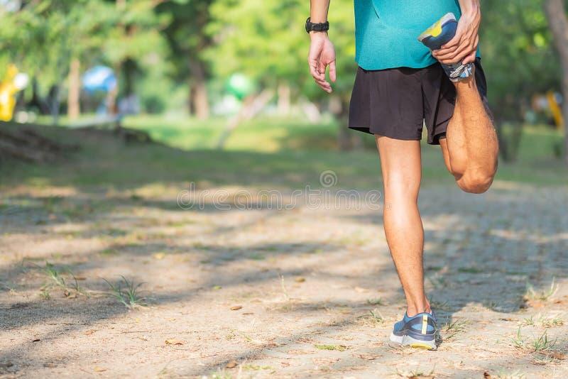 Den unga idrottsman nenmannen som sträcker i, parkerar utomhus- den manliga l?paren v?rmer klart f?r att jogga p? v?gen upp utanf arkivfoton
