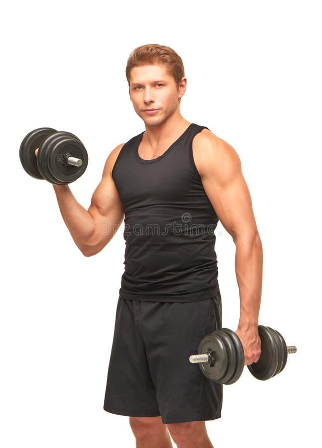 Den unga idrottsmannen som upp pumpar bicepen, tränga sig in med svarta hantlar royaltyfri fotografi