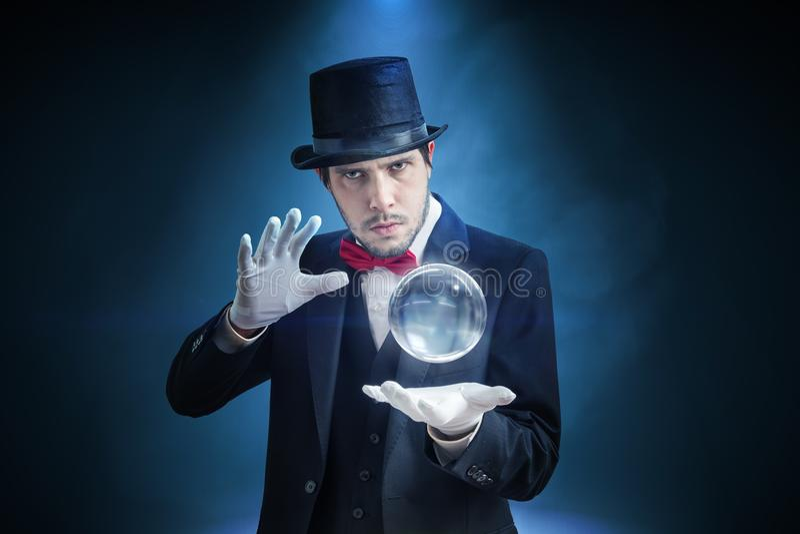 Den unga illusionisten, trollkarlen eller förmögenhetkassören förutsäger framtid med den crystal sfären royaltyfri fotografi