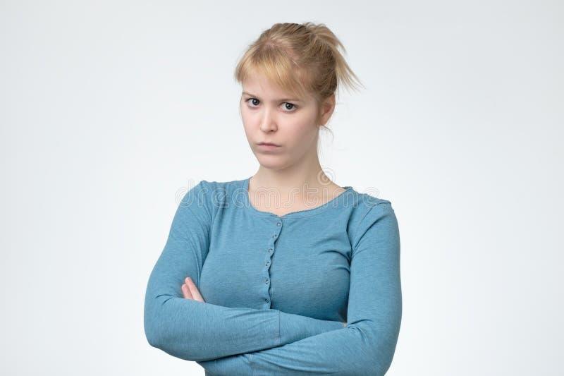 Den unga ilskna kvinnan i blå skjorta vek hennes armar royaltyfri bild