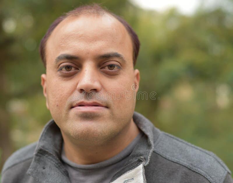 Den unga indiska mannen med att le poserar royaltyfri bild