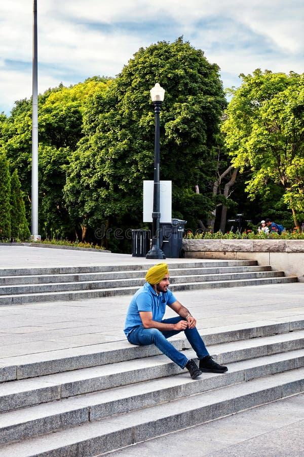 Den unga indiska sikhen som sitter på trappan av monteringskungliga personen, parkerar och talar på telefonen med hans hörlurar i royaltyfri bild