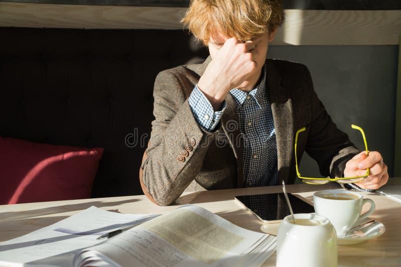 Den unga intelligenta mannen vilar av att göra arbets- eller universitetprojektuppgift på lunchtime i kafé royaltyfri foto