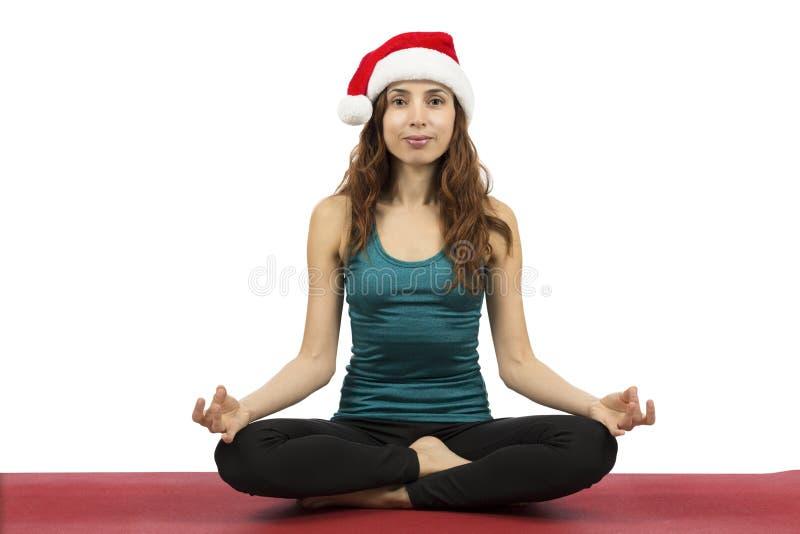 Den unga julkvinnan, i placerat, poserar i yoga fotografering för bildbyråer