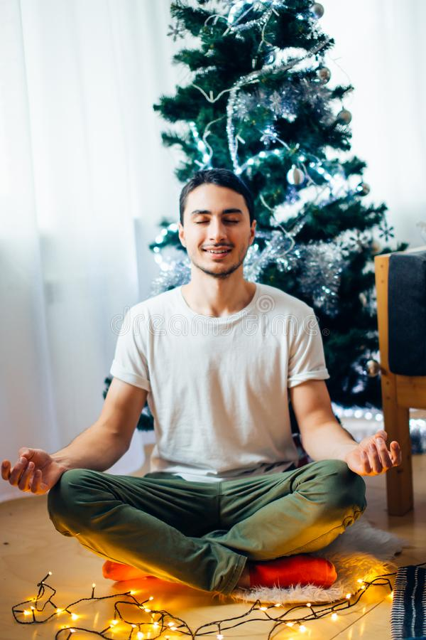 Den unga julmannen, i placerat, poserar i yoga nära julträd royaltyfria foton