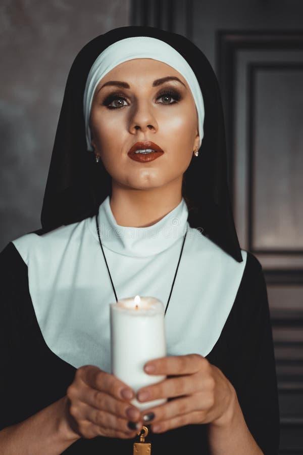 Den unga katolska nunnan rymmer stearinljuset i henne h?nder Foto p? svart bakgrund arkivbild