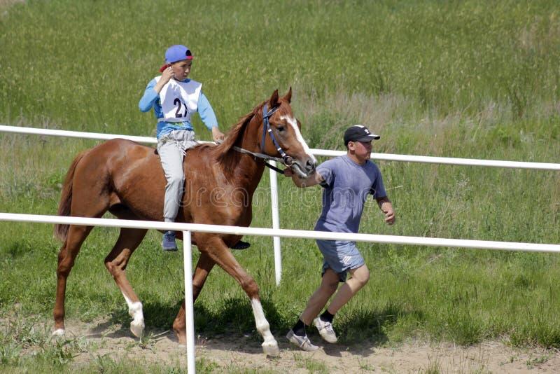 Den unga Kazakhpojken rider en ren breeded Kazakhhäst och förbereder sig för att springa med hans instruktör arkivbild