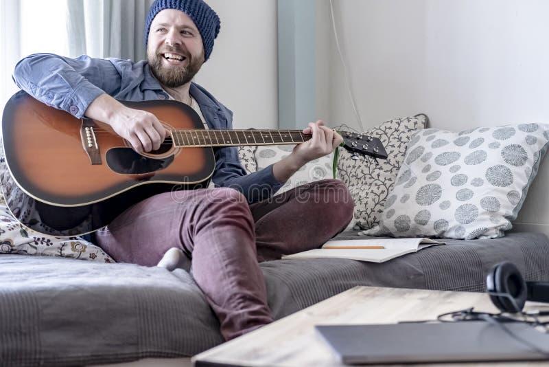 Den unga kompositören spelar den skriftliga musiken på den akustiska gitarren som behas med resultatet som ler lyckligt till hans royaltyfri foto