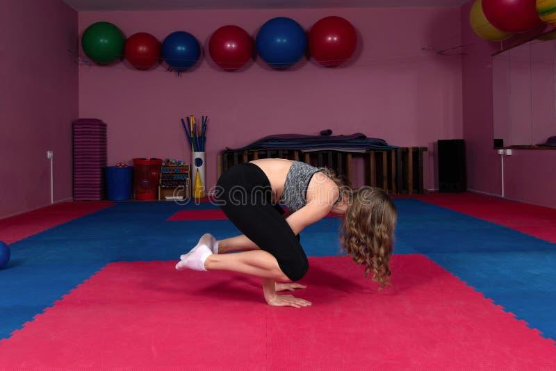 Den unga konditionidrottsman nen utför övningar i idrottshallen Bodybuilding arkivbilder