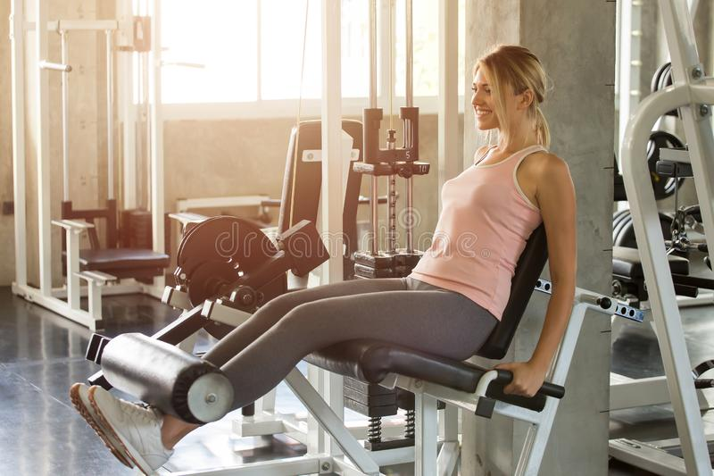 den unga konditionkvinnan i muskler för ben för sportswearövningar öppna med skjuter maskinen i idrottshall sund livsstil för spo royaltyfria bilder