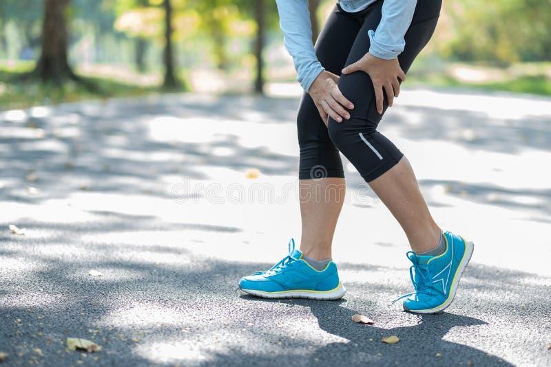 Den unga konditionkvinnan som rymmer hans sportbenskada, tränga sig in smärtsamt under utbildning Asiatisk löpare som har kalvkni royaltyfri fotografi