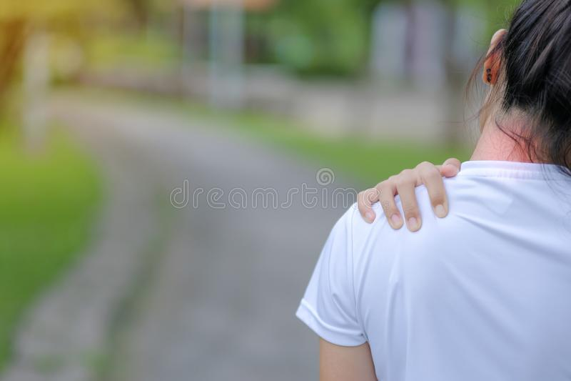 Den unga konditionkvinnan som rymmer hans sportskada, tr?nga sig in sm?rtsamt under utbildning Asiatisk löpare som har halsknip o arkivbilder