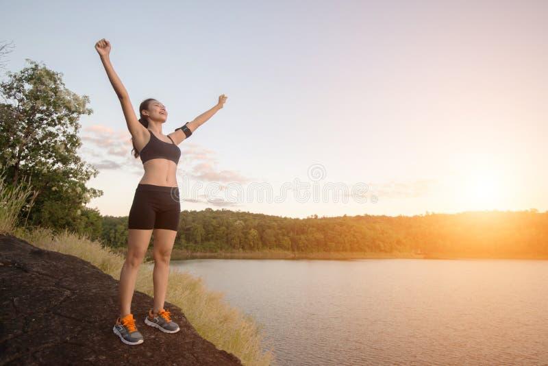 Den unga konditionkvinnan uppnår att fotvandra på maximum med sjösiktssolnedgång arkivfoton