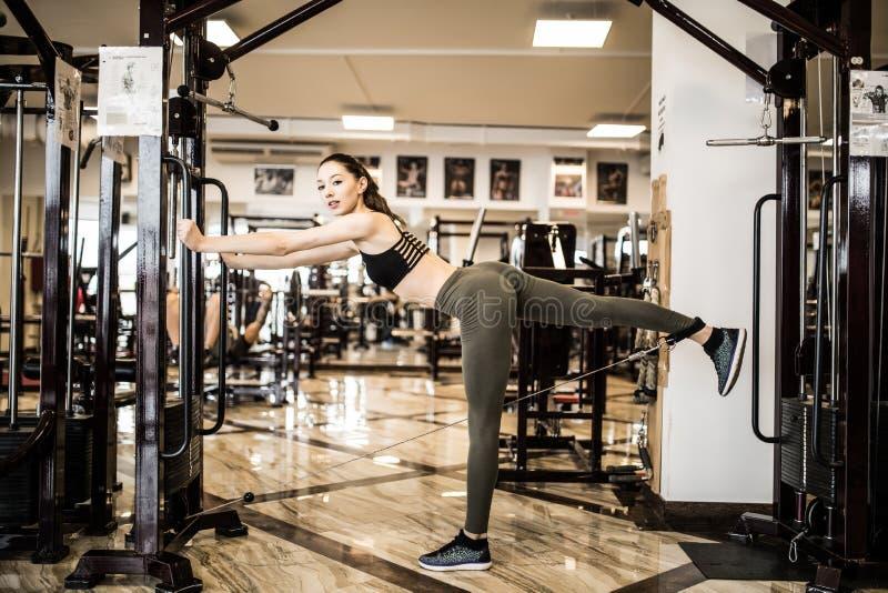 Den unga konditionkvinnan utför övning med övning-maskinen kabelövergång i idrottshall arkivbild