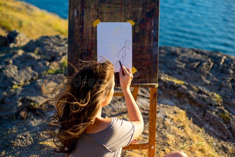 Den unga konstnären drar en seascape på solnedgången arkivfoto