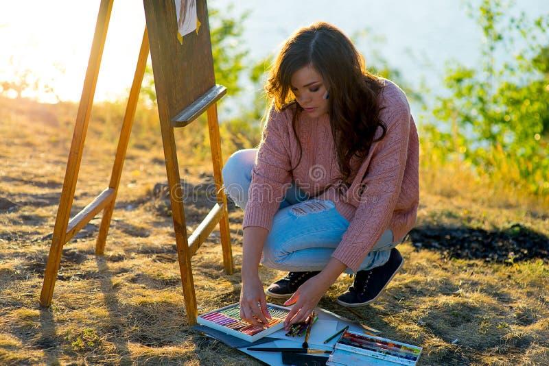 Den unga konstnären drar en seascape på solnedgången royaltyfri bild