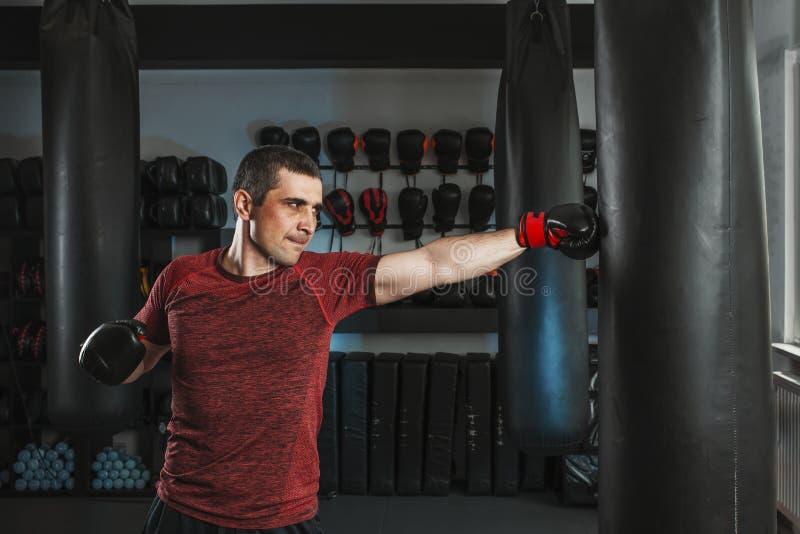 Den unga kort-haired mannen utbildar i en idrottshall med en stansa påse fotografering för bildbyråer