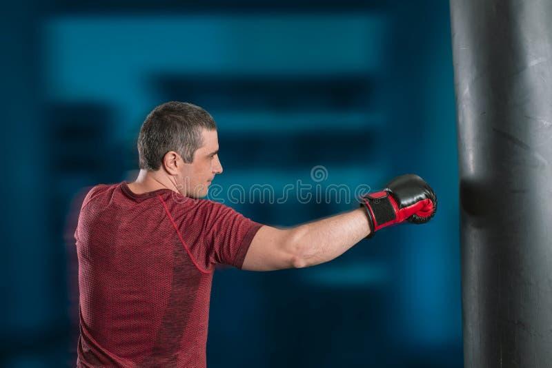 Den unga kort-haired mannen utbildar i en idrottshall med en stansa p?se arkivbild