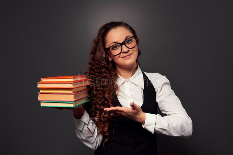 Den unga kvinnalärare, i att erbjuda för exponeringsglas, bokar royaltyfria bilder