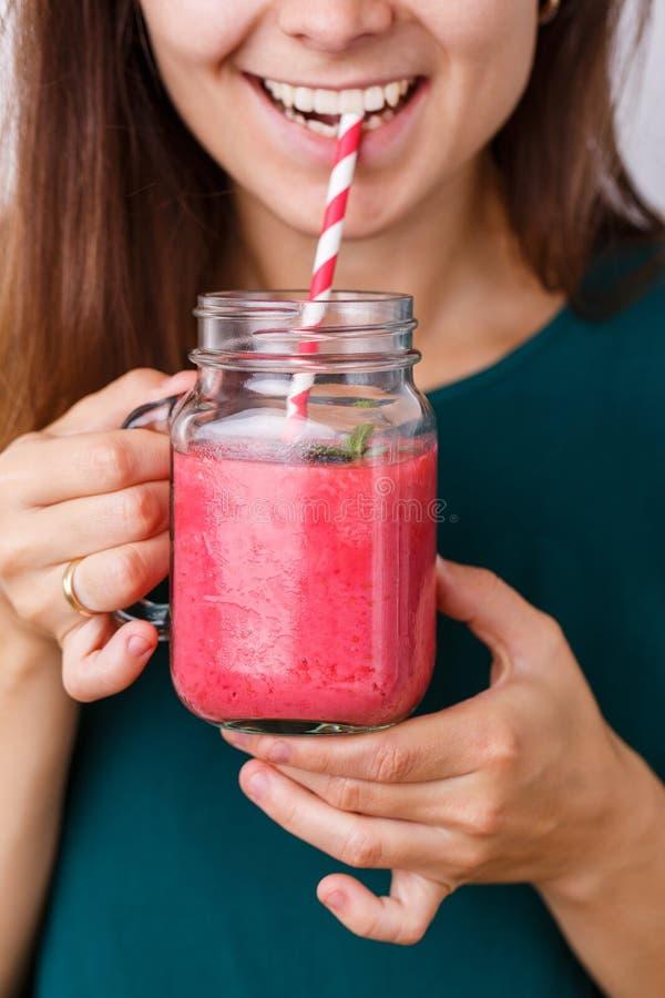 Den unga kvinnan är den hållande detoxdrinken, smoothie i den glass kruset arkivfoto