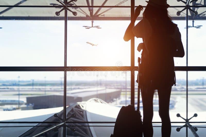 Den unga kvinnan är det stående near fönstret på flygplatsen och den hållande ögonen på nivån för avvikelse arkivbilder