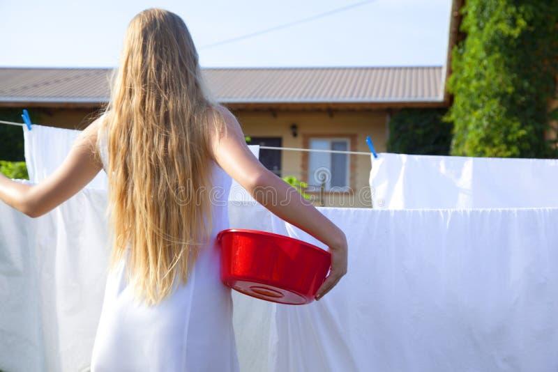 Den unga kvinnan är hängda upp vita ark på klädstreck Tonårig flicka med en plast- handfat arkivfoton