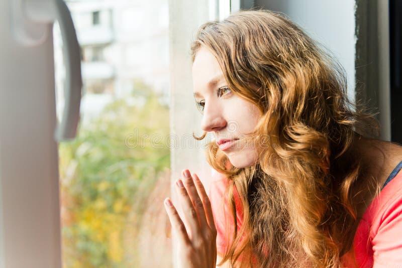 Den unga kvinnan är ledsen på fönstret royaltyfri foto