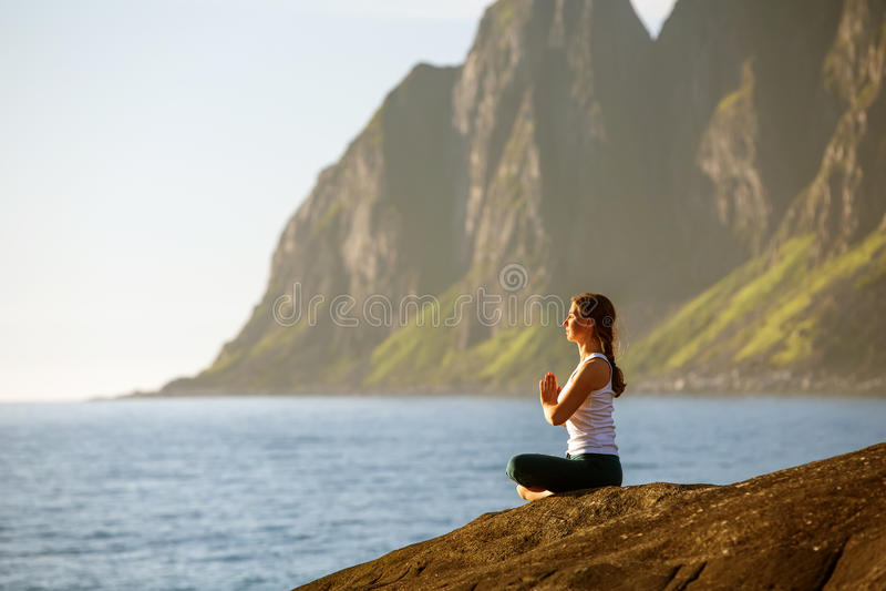Den unga kvinnan är praktiserande yoga mellan berg royaltyfri bild