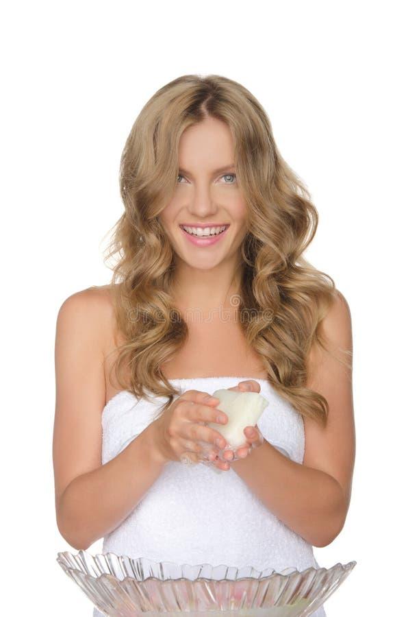 Den unga kvinnan är tvagningvatten med blommor arkivfoto